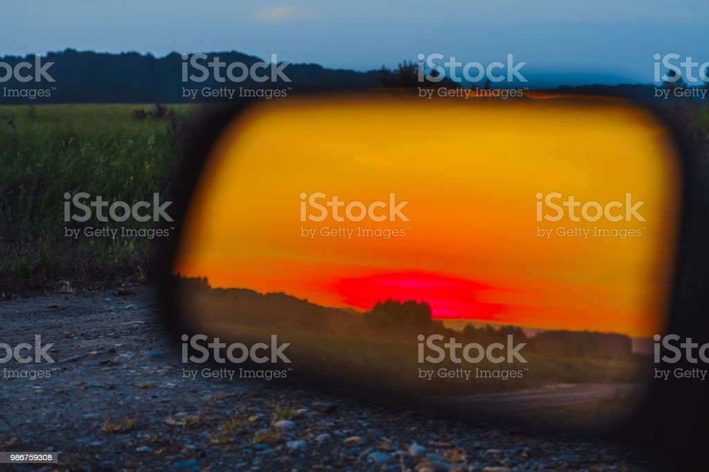 sunset in the mirror of the car stock photo