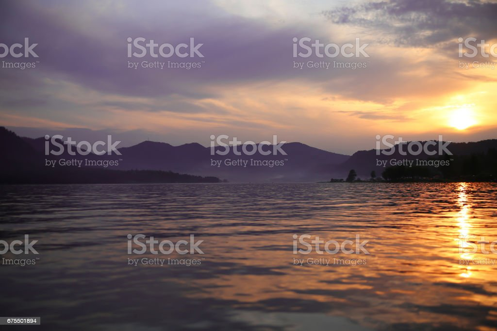 Sunset in the mountains of Altai. Dramatic sky, lake Teletskoe. The sunrise in the landscape of forest and pond. Purple fog over lake. Stunning views of nature. Twilight in mountains in a wooded area. royalty-free stock photo