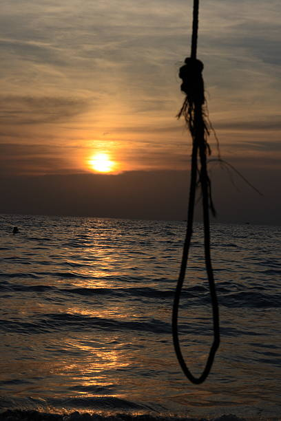 Sunset in the sea with a gallows stock photo