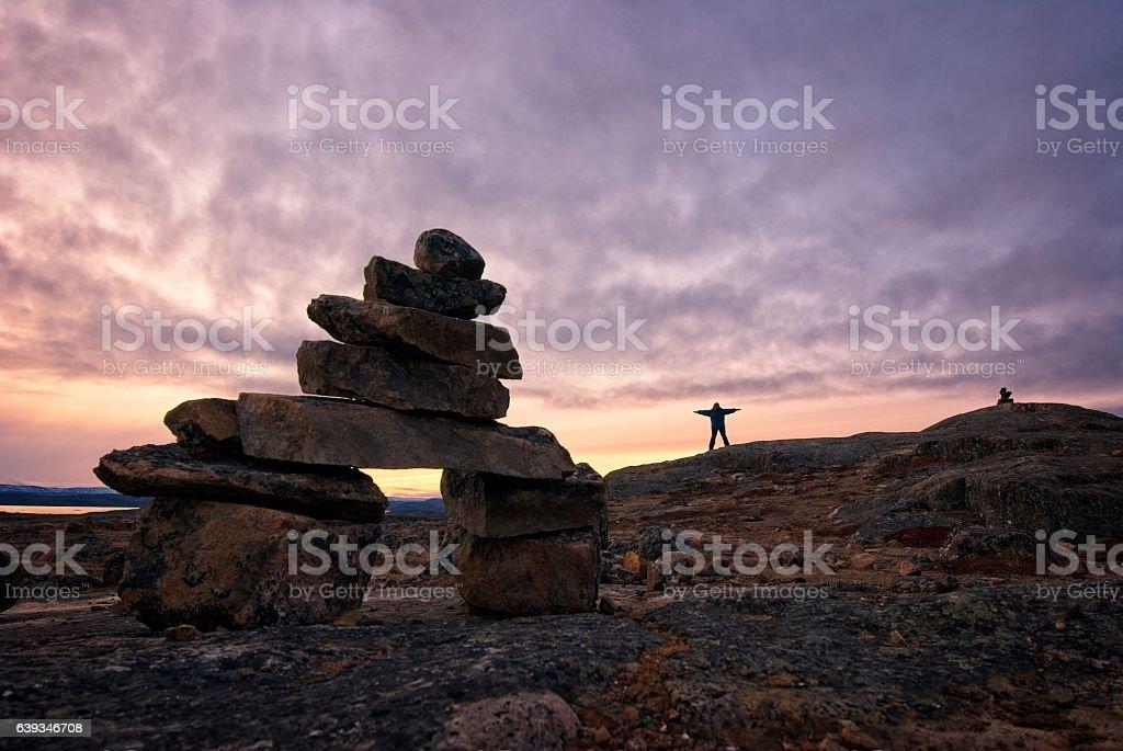 Sunset inukshuk on Baffin Island, Nunavut, Canada. stock photo