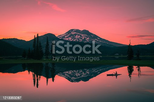 A lone kayaker paddles during a calm sunset on Sparks Lake outside of Bend, Oregon, Pacific Northwest
