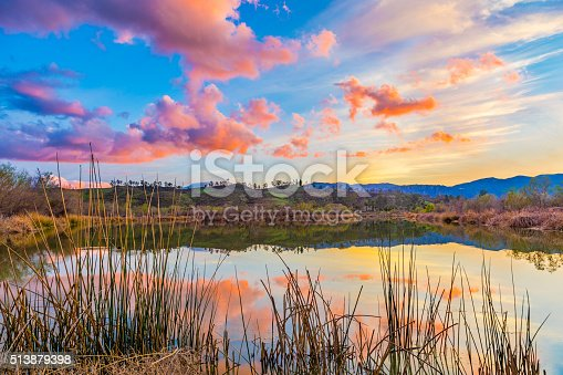Backlit reeds with calm water reflections fills the foreground leading back to the foothills of Southern California near Temecula with dramatic cloudscape at dusk