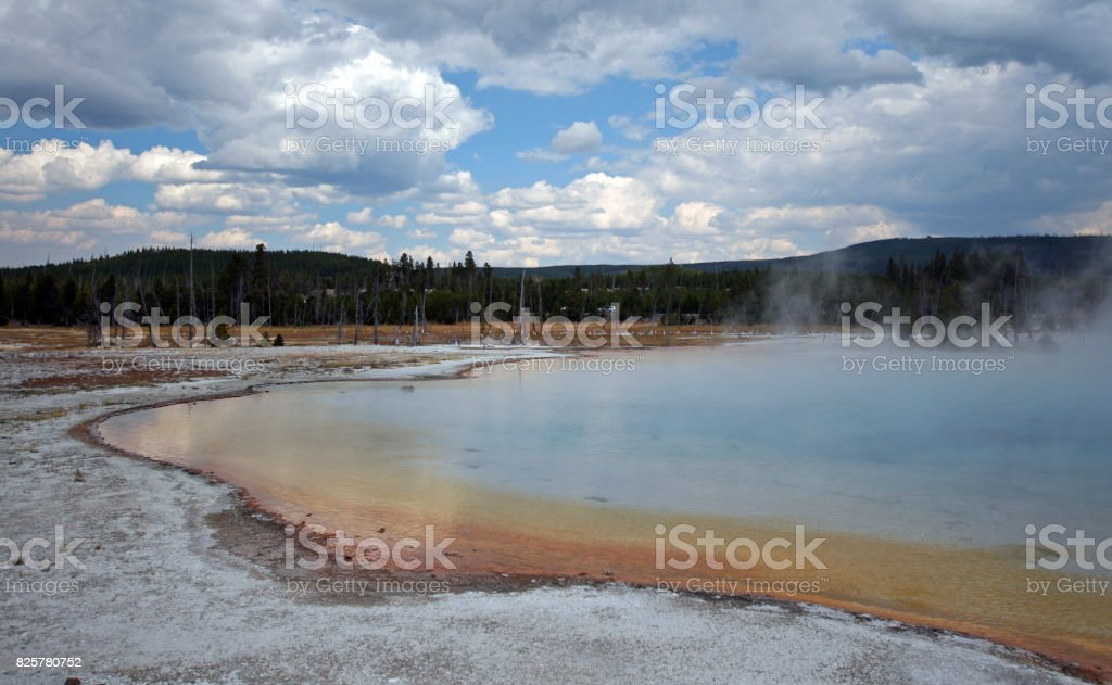 Sunset Lake under dark cumulus clouds in Black Sand Basin in Yellowstone National Park in Wyoming United States stock photo