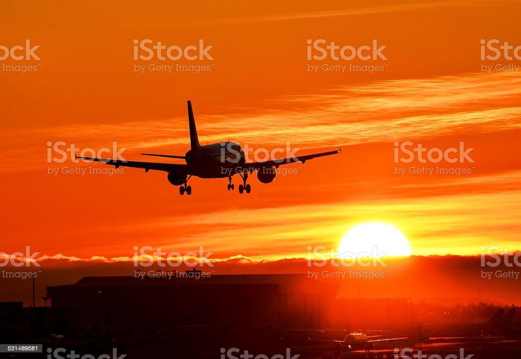 Sunset landing to runway stock photo