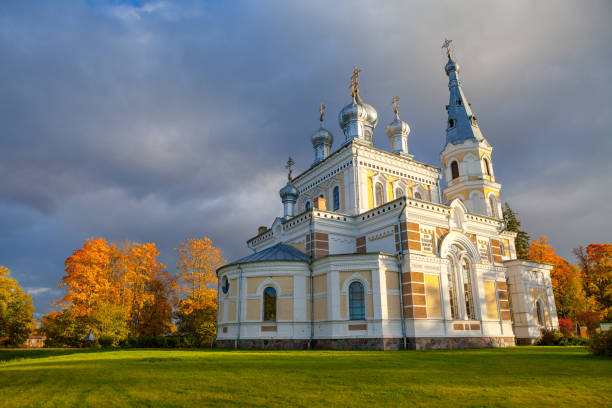 Sunset landscape of beautiful Orthodox church on the meadow, fall time. Stameriena, Latvia. stock photo