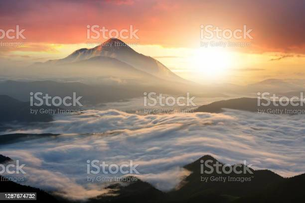 Photo of Sunset landscape with high peaks and foggy valley with thick white clouds under vibrant colorful evening sky in rocky mountains.