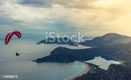 istock Sunset landscape with paragliding in the sky. Paraglider tandem flying over the Mediterranean with blue water and mountains in bright sunny day. Landscape of paraglider and Blue Lagoon, Oludeniz beach, Mugla, Turkey. Summer and holiday concept. 1135399213