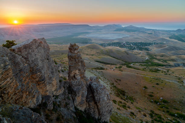 Sunset landscape with rocks and hills valley stock photo