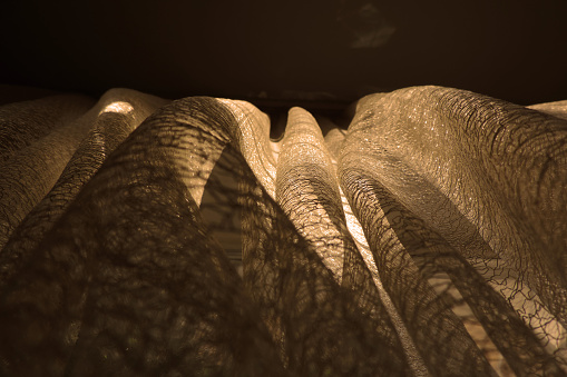 Sunset light and shadows from vintage lace tulle, bottom view,  Waves and creases in hanging fabric . Granny's cozy home. Retro interior.  Partial blurred