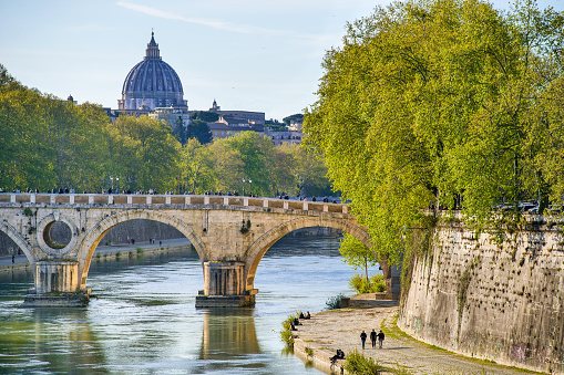Rome, Italy, April 09 -- A sunset light illuminates the ancient Ponte Sisto and the banks of the Tiber river, in the Trastevere district. In the background the unmistakable silhouette of the dome of St. Peter's Basilica. This bridge, one of the oldest in Rome, was rebuilt on a Roman structure at the behest of Pope Sixtus IV. Image in high definition format.