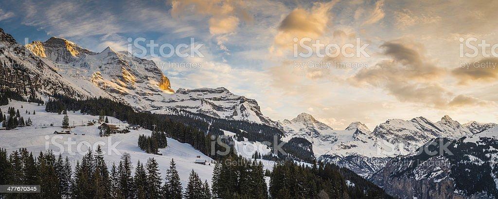 Sunset light illuminating snowy mountain ski resort Alps Switzerland royalty-free stock photo