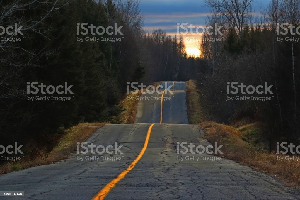 Sunset light on bumpy country road stock photo