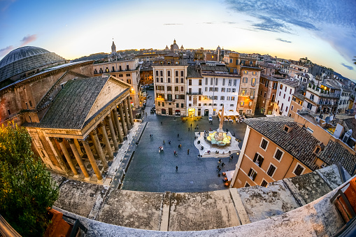 Rome, Italy -- A sunset light view from the rooftops of the iconic Piazza della Rotonda quarter, in the heart of Rome. At left the famous Pantheon with his dome and colonnade, one of the best preserved Roman structures in the Eternal City. The Pantheon was built in 27 b.C. by the Consul Marco Vispanio Agrippa for the emperor Augustus and dedicated to all Roman gods. Currently the Pantheon it is home to a Catholic church and inside there are the tombs of some Italian kings and the remains of the great Renaissance artist Raffaello Sanzio (Raphael). The fountain in the center of the square with an original Egyptian obelisk was built by the sculptor Leonardo Sormani in 1575 to a design by the architect Giacomo della Porta. Image un High Definition Format.