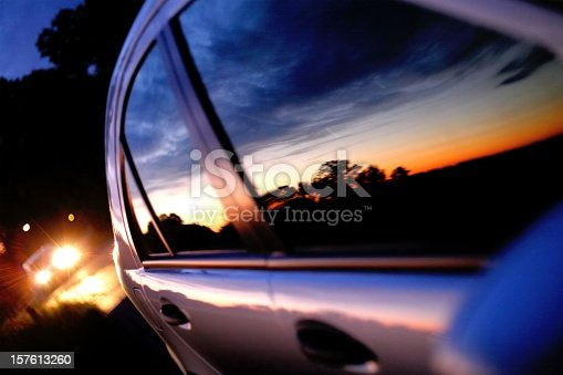 close up of a Sunset mirror on a car window at the blue hour, shallow depth of field, soft fokus is in the left area, low key
