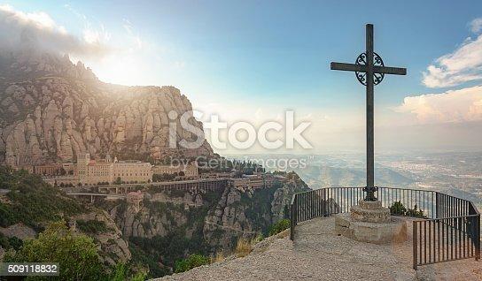 Christian cross from Montserrat Mountain viewpoint at sunset. View to the Monserrat Monastary  in the mountains. Famous Monastary near Barcelona, Catalonia, Spain.