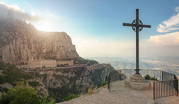 Sunset Montserrat Monastery Catalonia Christian Cross Christian cross from Montserrat Mountain viewpoint at sunset. View to the Monserrat Monastary  in the mountains. Famous Monastary near Barcelona, Catalonia, Spain. abbey monastery stock pictures, royalty-free photos & images