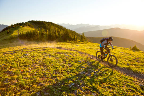 Sunset Mountain Bike Ride A male teenager rides his mountain bike in the Rocky Mountains of Canada. He is riding an enduro-style mountain bike and wearing a hydration backpack. mountain biking stock pictures, royalty-free photos & images