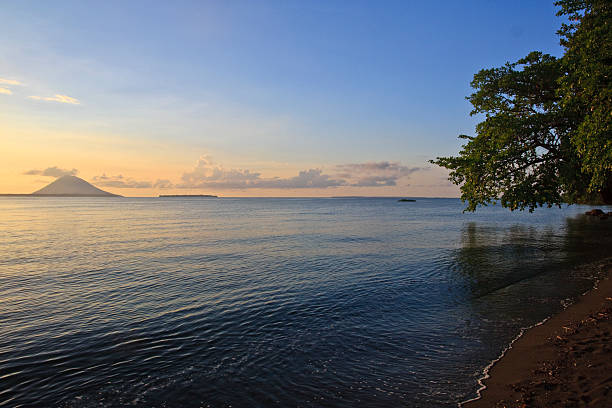 Sunset near Bunaken Indonesia Sunset on beach near Manado Indonesia with volcano in distance manado stock pictures, royalty-free photos & images