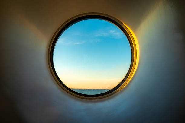 Sunset ocean view of horizon seen from inside of a cruise ship cabin window. stock photo