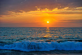 A Colorful Ocean Sunset Sky as a Gentle Wave Rolls to Shore
