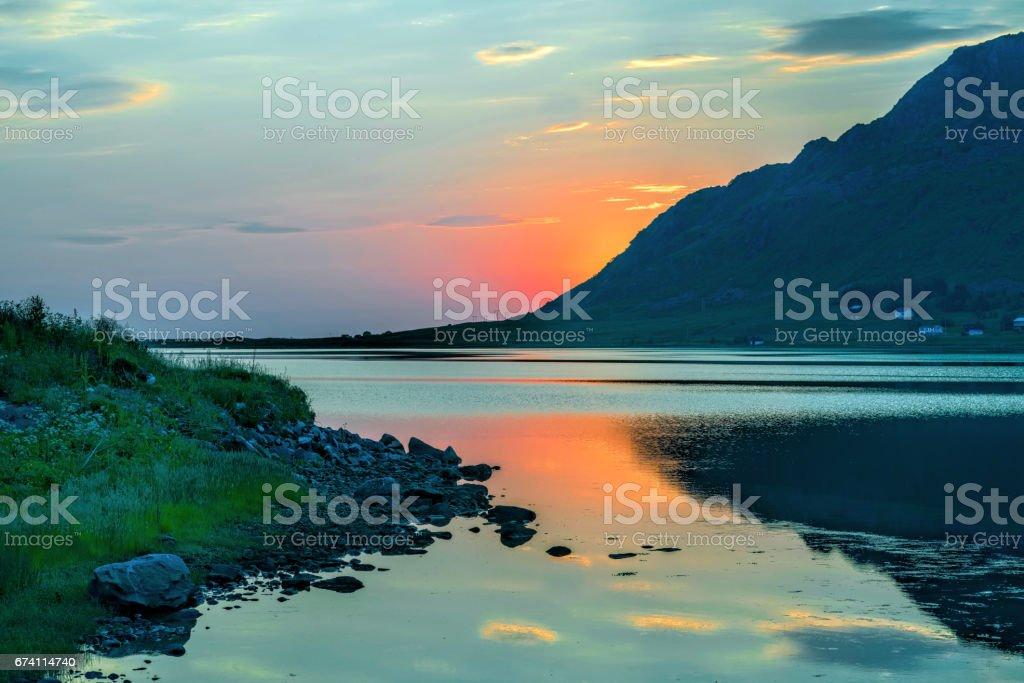 Sunset of midnight sun behind mountains at fjord of Lofoten, Norway royalty-free stock photo