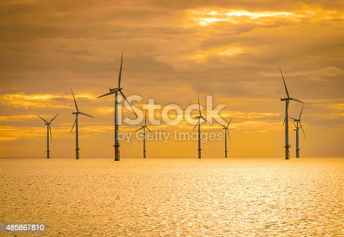 istock Sunset Offshore Wind Turbine in a Wind farm under construction 485867810