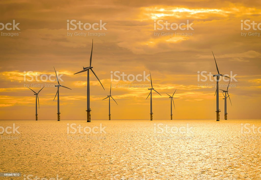 Sunset Offshore Wind Turbine in a Wind farm under construction stock photo