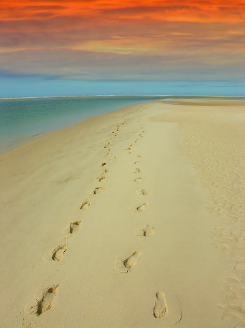 A couple walked on this deserted beach at sunset, their footprints can be seen on the sand