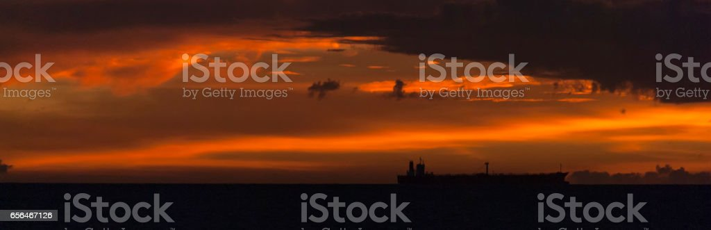 Sunset on a beach with a oil tanker. stock photo