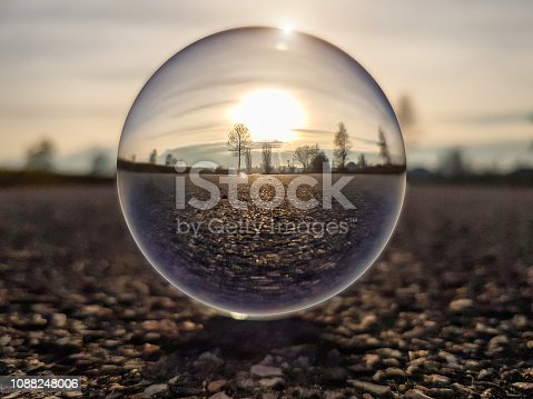Sunset on a country road through a lens ball (crystal ball) - Italy