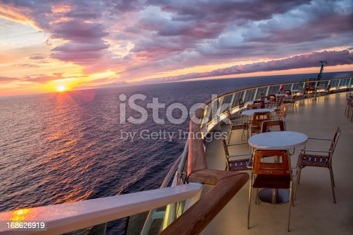 Sunset on a cruise ship with tables and chairs.  Carefully shot scene making sure that no copyrighted ship design is depicted.Sunset on a cruise ship with tables and chairs.  Carefully shot scene making sure that no copyrighted ship design is depicted.