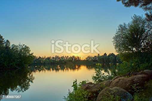 Sunset on a lake with blue water and sky, in the foreground sage and round stones
