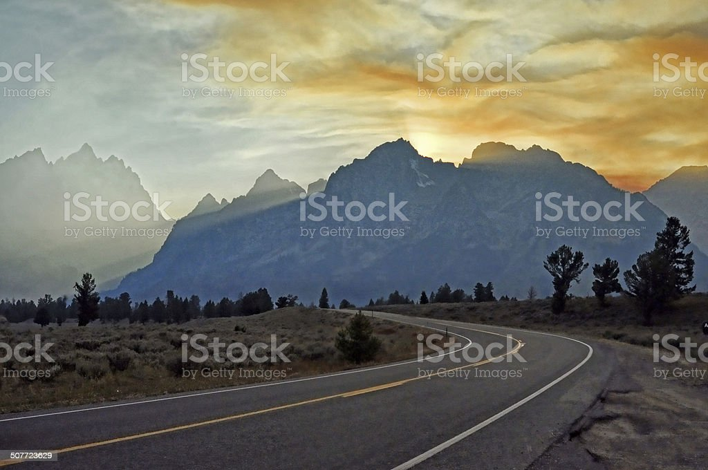 Sunset on a lonely highway in The Grand Tetons. stock photo