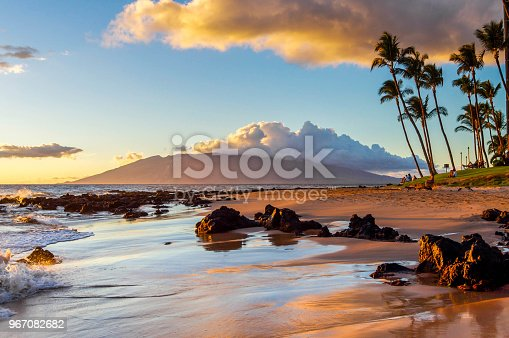 The glow of sunset is reflected on a Maui beach.
