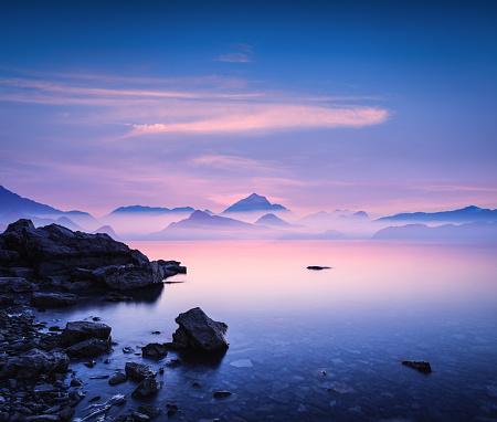 Tranquil landscape at sunset with sea and mountains in the distance.