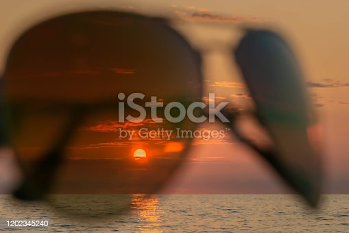 Setting sun, evening sky, and sea through sunglasses in seacoast. Sundown in sea through eyeglasses. Concept of summer holidays with beach scene in sunset through sunglasses