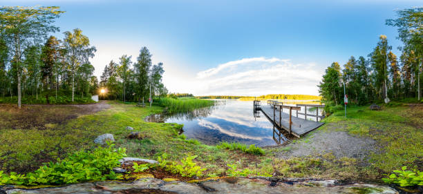 Sunset on Forest Clearing with Calm Lake and Wooden Footbridge Blue Sky stock photo
