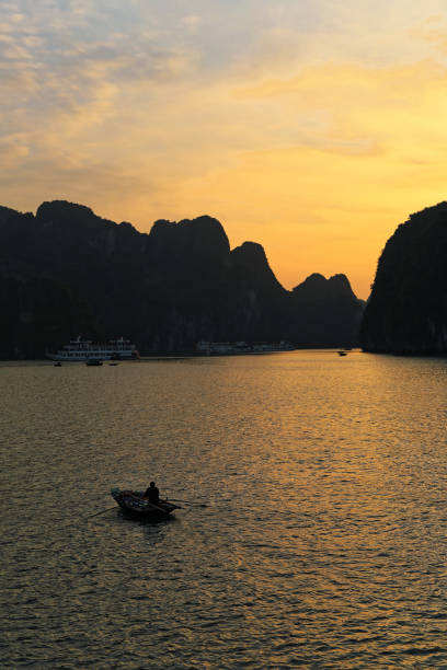 Sunset on Ha long bay with back lit rowing boat