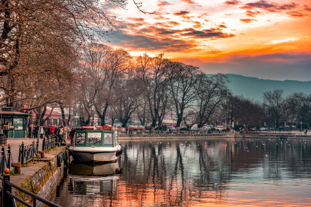 Sunset on lake Pamvotis. Docked boat ready to transfer people to the small island. Greece. stock photo