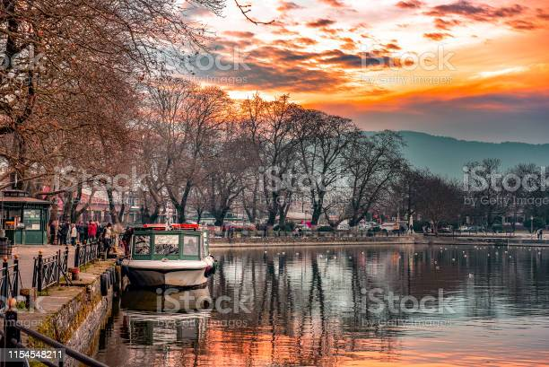 Photo of Sunset on lake Pamvotis. Docked boat ready to transfer people to the small island. Greece.