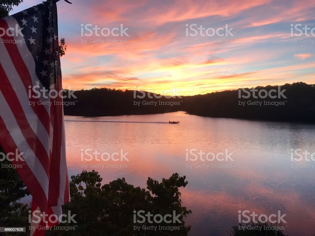 Sunset on lake with fishing boat stock photo