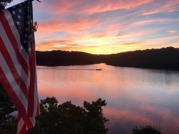 Sunset on lake with fishing boat stock photo