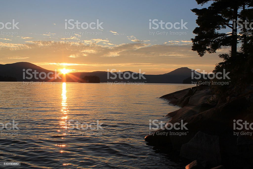 Sunset on lake with pine trees - no flare stock photo