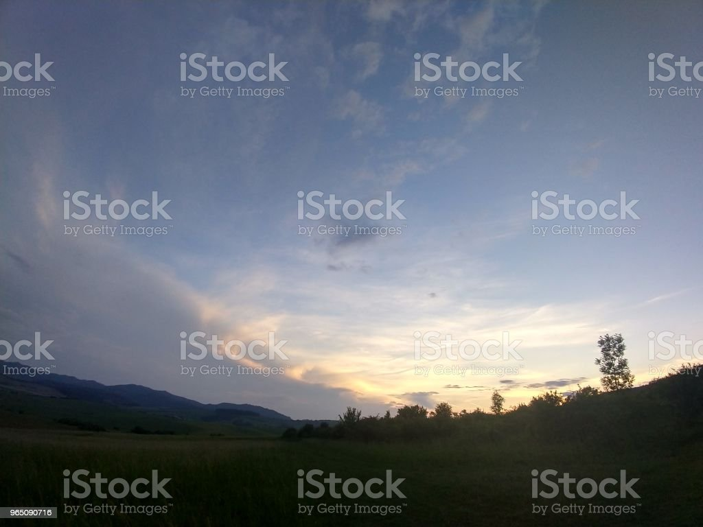 Sunset on meadow with hills and tree. royalty-free stock photo