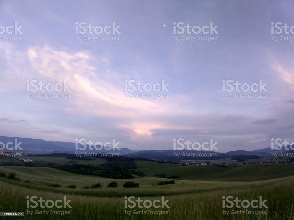 Sunset on meadow with hills and tree. zbiór zdjęć royalty-free