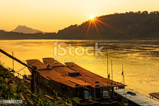 Sunset over the mighty Mekong River in Luang Prabang, Laos.  This stunning view is from the riverbank looking towards Chompet district across the river.  The entire town of Luang Prabang was declared a UNESCO world heritage site in 1995.