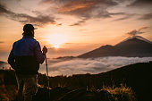 One man, standing high on beautiful mountain Batur in sunset alone.