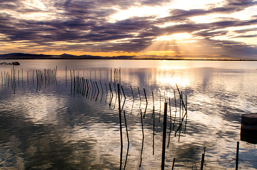 Sunset on one day cloudy in the famous lake of the albufera of Valencia, Spain with a boat in the front