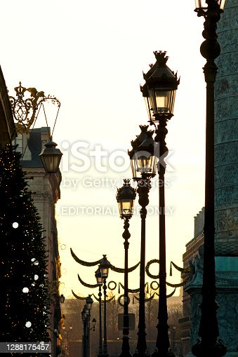 Sunset on Place Vendôme during Christmas, with Christmas tree and floor lamp in Paris, France - November 27, 2020