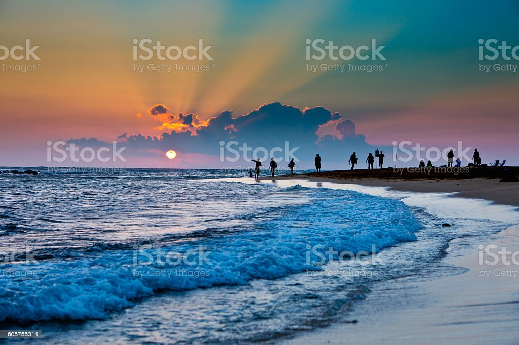 Sunset on Poipu Beach with sightseers in Kauai Hawaii stock photo